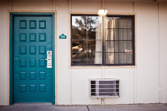 Modré vchodové dvere vedľa veľkého okna na bielom dome