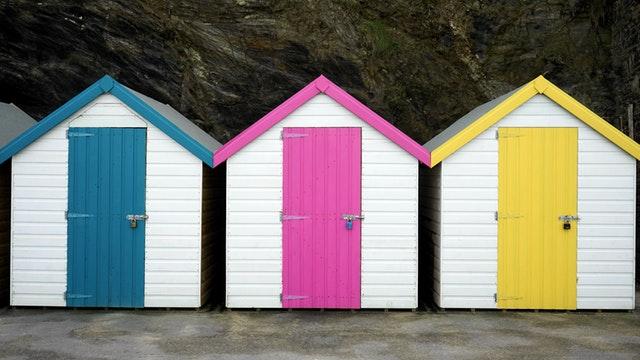 Tri biele domčeky s ružovými, modrými a žltými dverami