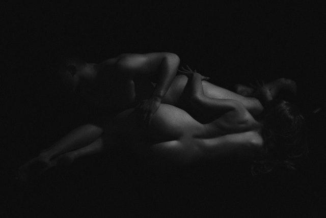 Nahý muž a žena ležia v objatí v tme.jpg
