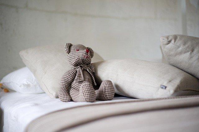 Plyšový medveď medzi vankúšmi na posteli